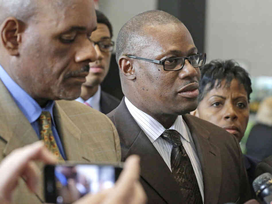 Illinois state Rep. Derrick Smith (center) speaks to reporters at the federal building Tuesday after a jury convicted him of bribery.