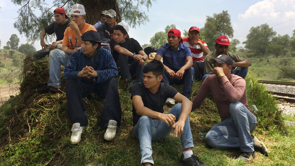Migrants from Central America rest alongside the railroad tracks outside Huehuetoca. The group is waiting to jump aboard a freight train headed toward the U.S. border. Of the 15, there are three minors, all traveling alone. (NPR)