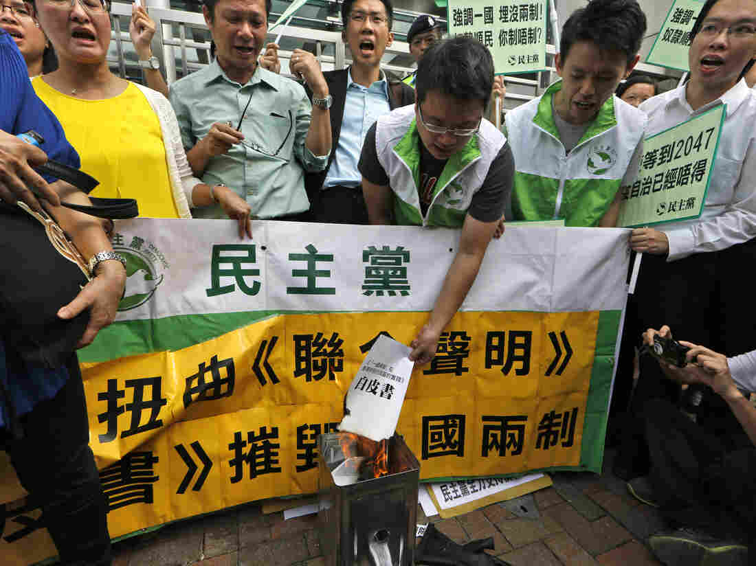 """Protesters burn a mock """"white paper"""" released by China's State Council on Tuesday, which says Beijing holds ultimate control over the former British colony."""