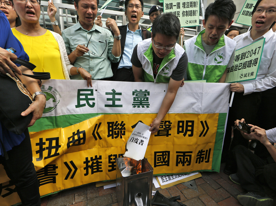 "Protesters burn a mock ""white paper"" released by China's State Council on Tuesday, which says Beijing holds ultimate control over the former British colony. (Kin Cheung/AP)"