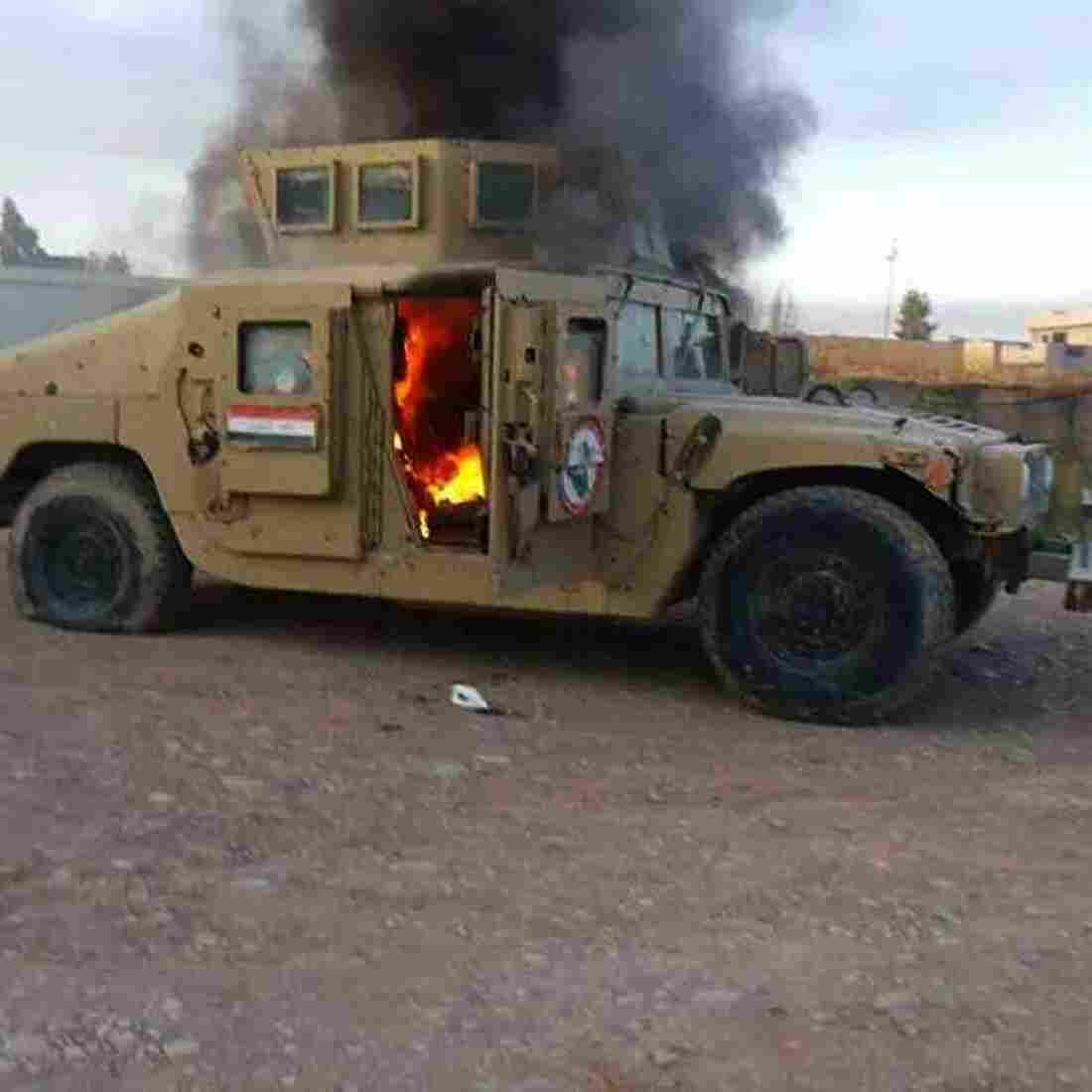 A cellphone photo shows an armored vehicle belonging to Iraqi security forces in flames Tuesday, after hundreds of militants launched a major assault in Mosul. Some 500,000 Iraqis have fled their homes in the large city since militants took control.