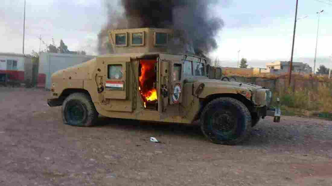A cellphone photo shows an armored vehicle belonging to Iraqi security forces in flames Tuesday, after hundreds of militants launched a major assault in Mosul. Some 500,000 Iraqis have fled their homes