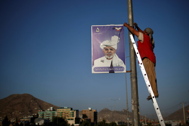 A man removes a poster of presidential candidate Ashraf Ghani after the official end of the election campaign. Saturday's runoff election pits Ghani against Abdullah Abdullah. Both have held top government positions and want close ties with the U.S.