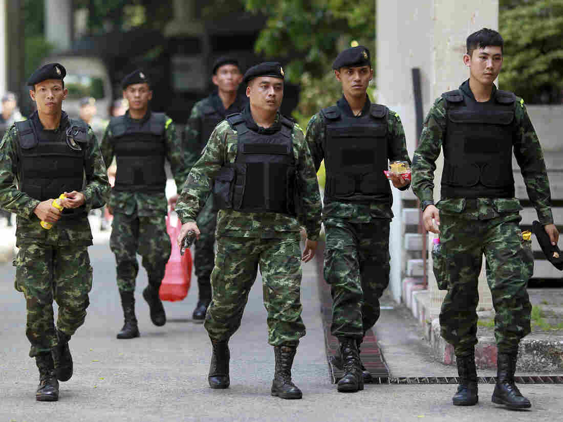 Thai soldiers walk after being deployed to guard Bangkok's Victory Monument against anti-army protests, on Sunday. The ruling junta is now insisting that foreign journalists not call the military takeover a coup.