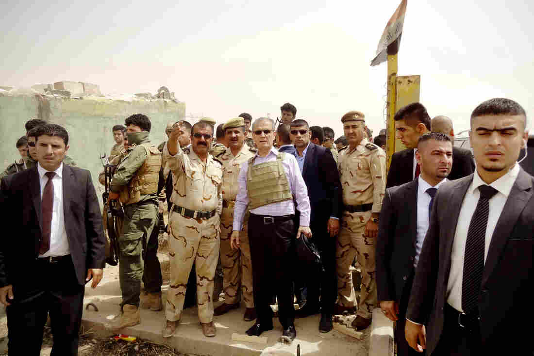 Kirkuk province's Kurdish governor, Najim al-Din Omar Karim (center, wearing a bulletproof vest), listens to a commander of the Kurdish Peshmerga forces as troops are deployed on the main road between Kirkuk, Mosul and Baiji in response to the offensive by ISIS, an extremist Islamist group.