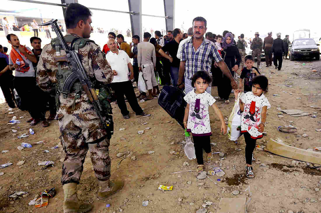 A Kurdish policeman stands guard while refugees from Mosul head to Irbil, Iraq, about 217 miles north of Baghdad in the self-ruled northern Kurdish region.