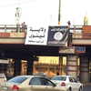 A banner bearing a black flag used by the al-Qaida-linked Islamic State of Iraq and Syria hangs from an overpass in Mosul, Iraq. The picture was posted Thursday on a militant Twitter account, and was authenticated by The Associated Press. Iraqi officials say ISIS militants also captured two towns in the ethnically mixed Diyalah province.