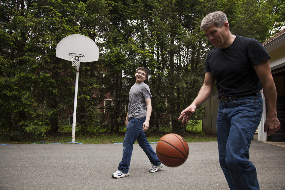Ed Damiano and his son David,  15, play basketball at home in Acton, Mass. Ed has invented a device he hopes will make David's diabetes easier to manage. (Ellen Webber for NPR)