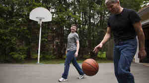 Ed Damiano and his son David,  15, play basketball at home in Acton, Mass. Ed has in
