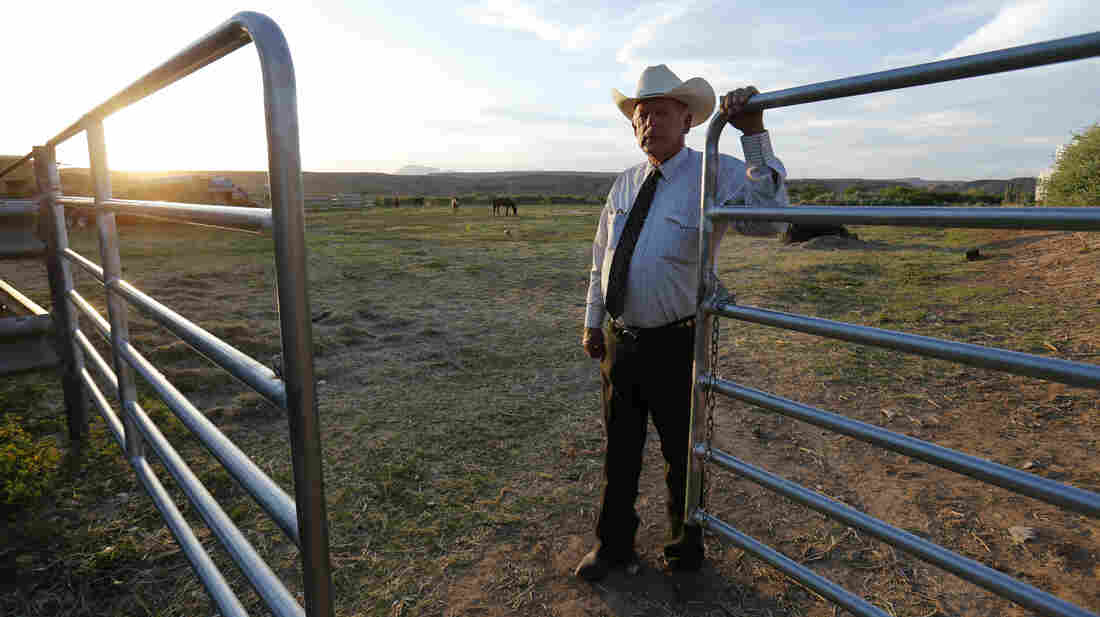 Rancher Cliven Bundy stands near a gate on his 160-acre ranch in Bunkerville, Nev., the site of a standoff with the government last month. If the federal government comes back, Bundy promises, his militia supporters will also return in force.