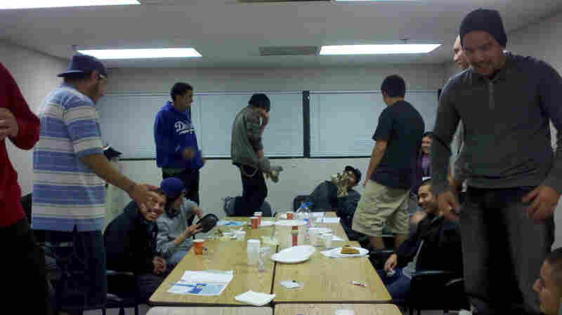 Members of the L.A. Fathers Program practice a role-playing exercise — standing on chairs and yelling to see what it feels like when an adult yells at a child.
