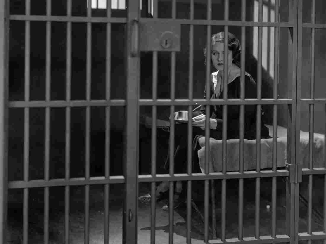 Circa 1925: A prisoner stares forlornly through the bars of her prison cell.