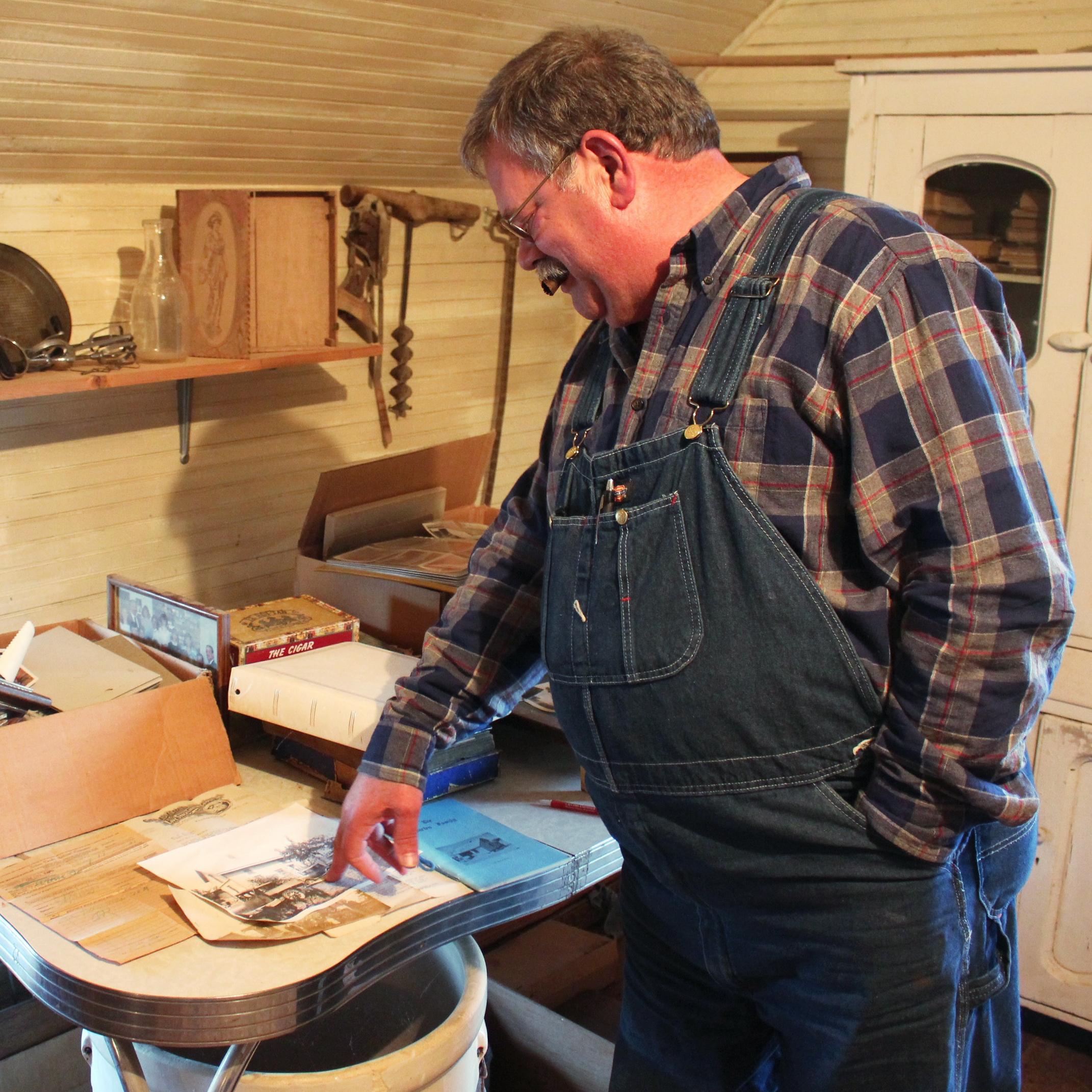 Donn Teske looks through family heirlooms in a house where his ancestors lived near Wheaton, Kans.