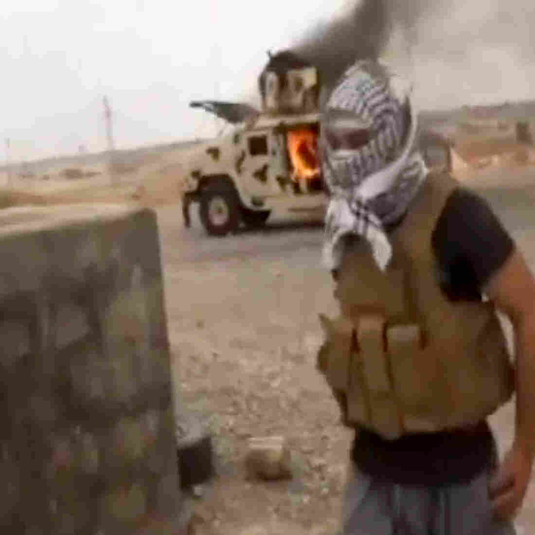 This video image posted last week by Iraqi0Revolution, a group supporting the Islamic State of Iraq and Syria, purportedly shows a militant standing in front of a burning Iraqi army vehicle in Tikrit, Iraq.