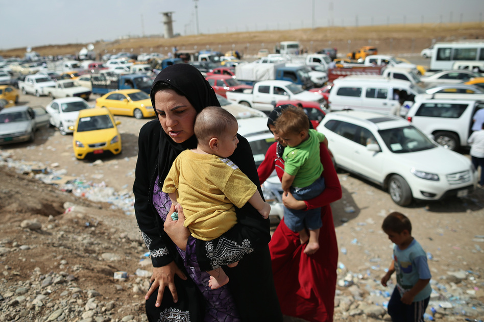 Families arrive at a checkpoint next to a temporary displacement camp on Friday in Kalak, in northern Iraq. Thousands of people have fled Iraq's second-largest city, Mosul, after it was overrun by Sunni militants.