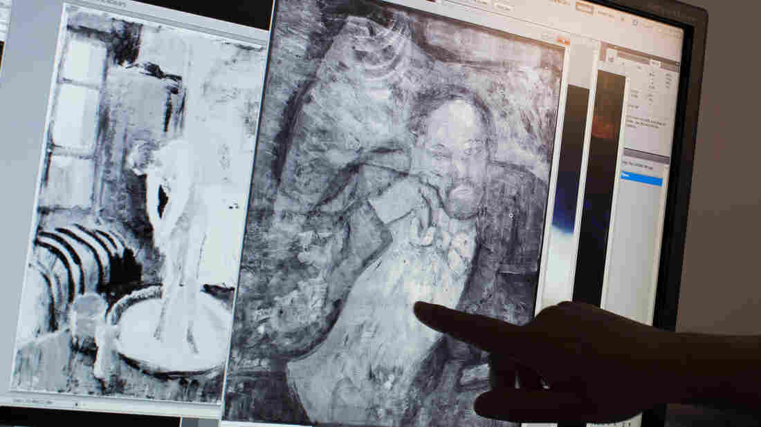 Scientists and art experts found a hidden painting beneath one of Picasso's first masterpieces, The Blue Room, thanks to advances in infrared technology. Here, associate conservator Patricia Favero of The Phillips Collection points to a detail in the image.