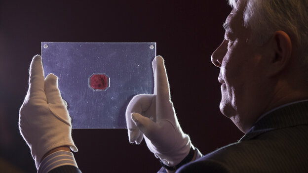 """David Redden of Sotheby's auction house holds a case containing the sole surviving """"British Guiana One-Cent Black on Magenta"""" stamp dating from 1856."""