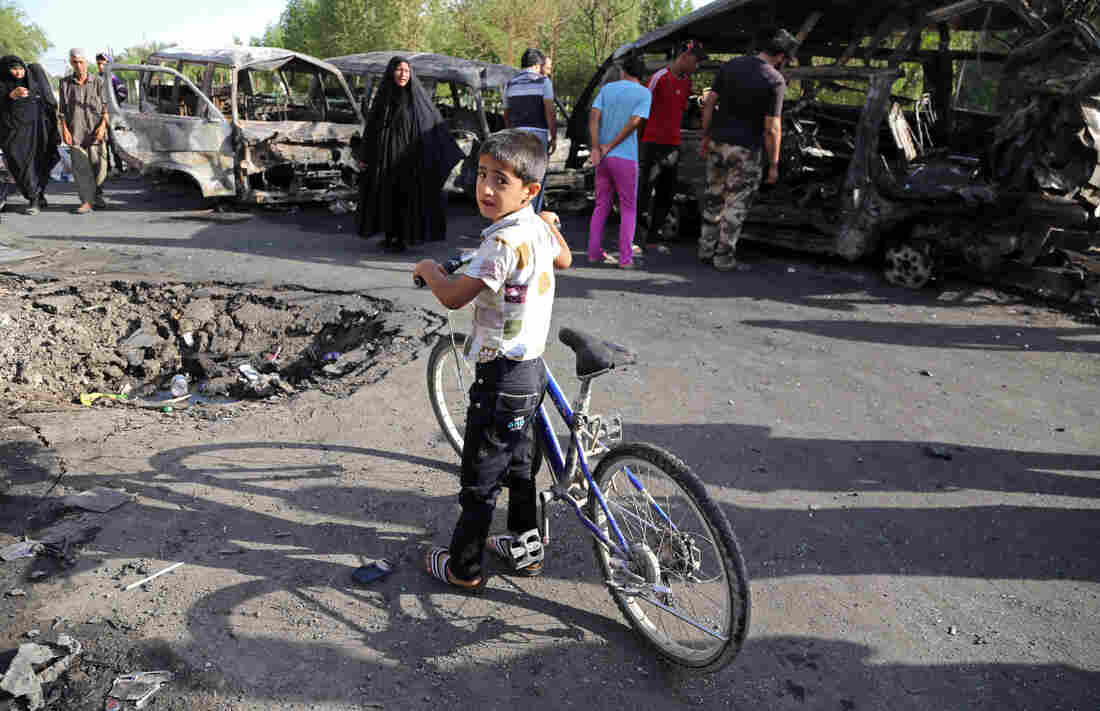 An Iraqi boy and other civilians look at the aftermath of a car bomb in Baghdad's Sadr City on Wednesday. The violence in the Shiite district comes as Sunni militants advance in northern Iraq.