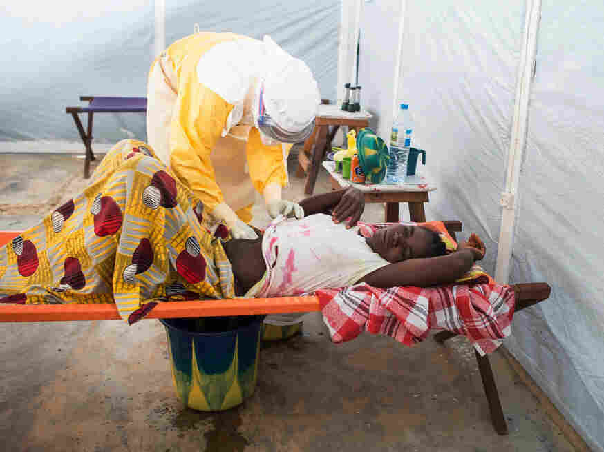 A health worker from Doctors Without Borders examines Ebola patient Finda Marie Kamano, 33, at her home in Conakry, Guinea, in April. The outbreak that began in February is still spreading in West Africa.