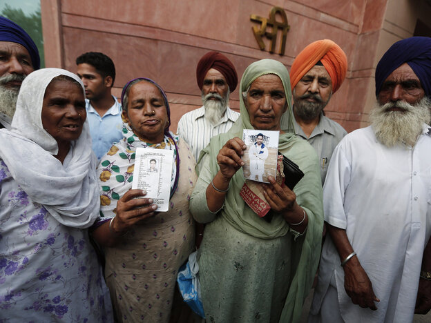 Relatives hold up photographs of Indian workers who have been kidnapped in Iraq.