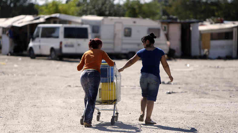 Women from the Roma community push a shopping trolley containing water toward their camp in Sucy-en-Brie, near Paris, in a photo from 2012.