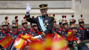 King Felipe VI greets well-wishers as he arrives at the Royal Palace in Madrid fo