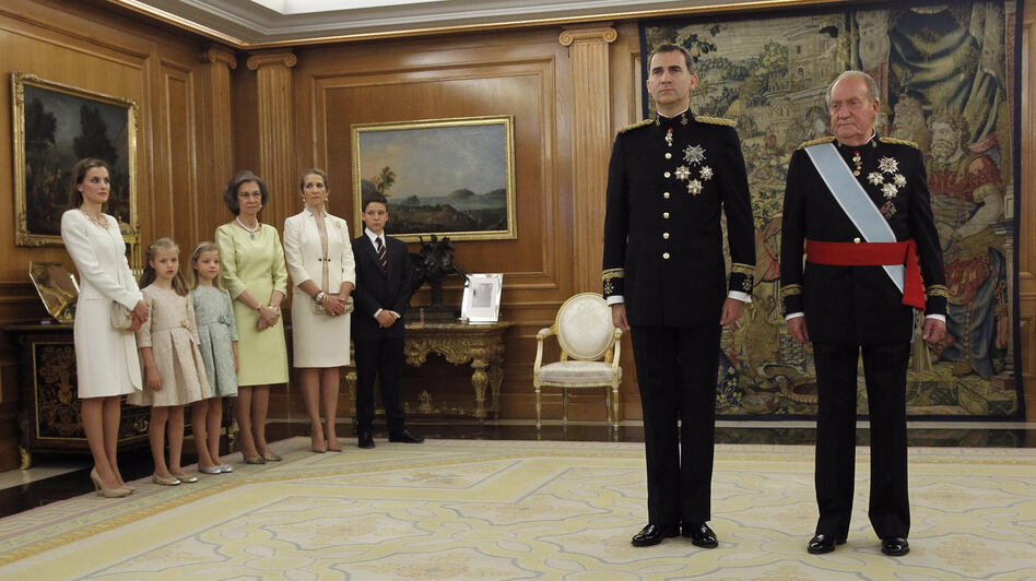 King Felipe stands next to his father, the former King Juan Carlos, while members of the royal family look on.