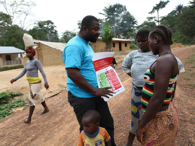 A UNICEF field worker talks to villagers in Liberia's Foya District about how to prevent Ebola disease.