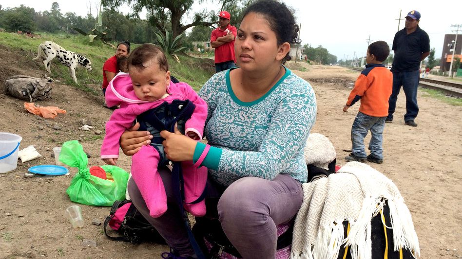 Amalia Diaz, a 22-year-old from Honduras, holds her 5-month-old daughter, Shilin, as they wait in Tequixquiac, Mexico, for a northbound train to pass. They plan to jump onboard and ride on top of the train all the way to the United States border.