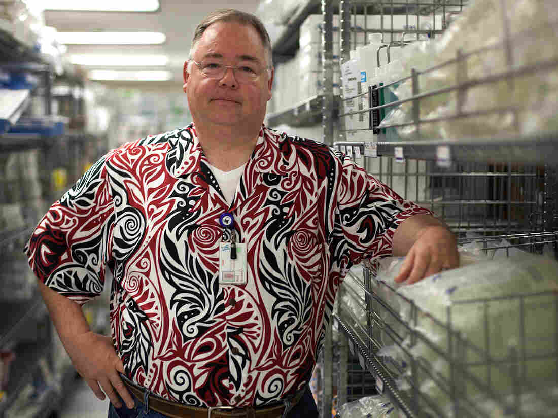 Reid Kennedy, materials manager at San Francisco General Hospital, stands next to racks of saline solution. He has had to carefully manage the hospital's supply of saline during this shortage.