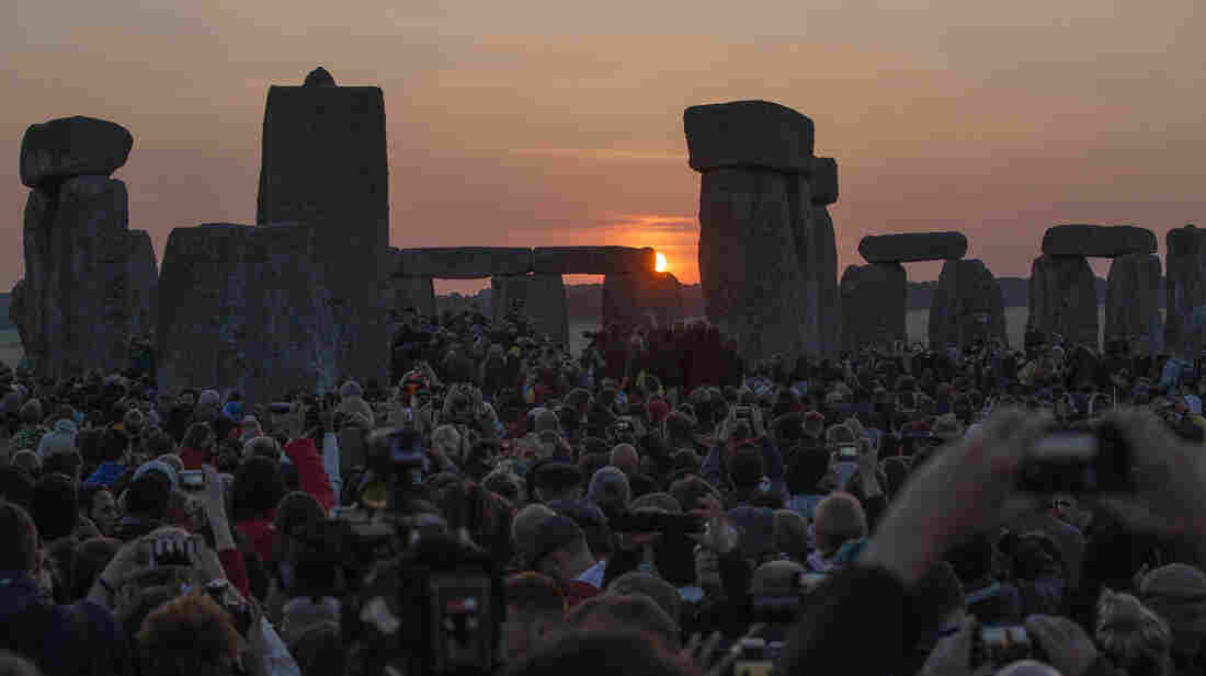 The sun rises as thousands of revelers gathered at the ancient stone circle Stonehenge, near Salisbury, England, to celebrate the summer solstice on Saturday.