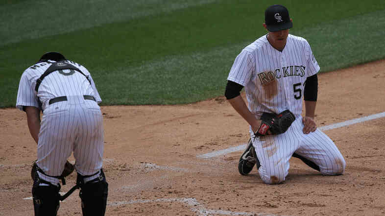 Starting pitcher Christian Friedrich and catcher Michael McKenry of the Colorado Rockies collect themselves after they allowed three runs to score on a wild pitch.