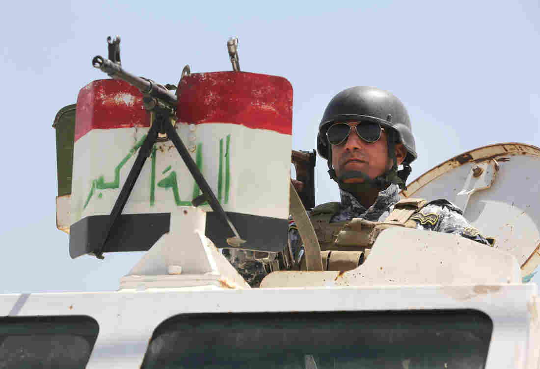An Iraqi federal policeman standing on top an armored vehicle secures a checkpoint in Baghdad, Iraq, on Sunday.