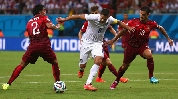 Clint Dempsey of the United States is chall