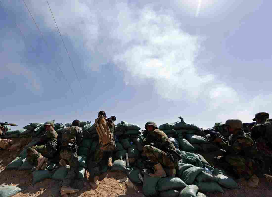 Iraqi Kurdish forces take position near Taza Khormato as they fight jihadist militants from the Islamic State of Iraq and Syria (ISIS) positioned five kilometers away in Bashir on Monday.