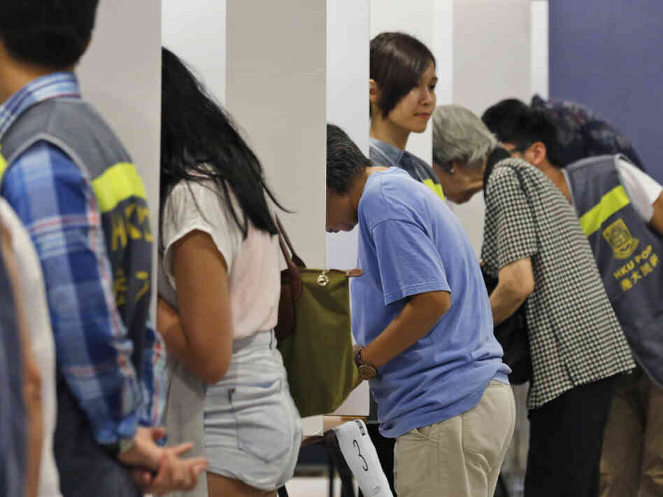 People vote Sunday at a polling station for an unofficial referendum on democratic reform in Hong Kong. Beijing has denounced the vote as illegal.