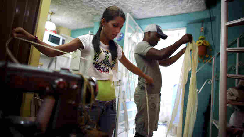 Cuban entrepreneur Barbara Fernandez Franco oversees two employees in the small living room of her home in Havana, the Cuban capital. Her boyfriend, Michel Perez Casanova (right), works in the tourism industry but also helps with her business.