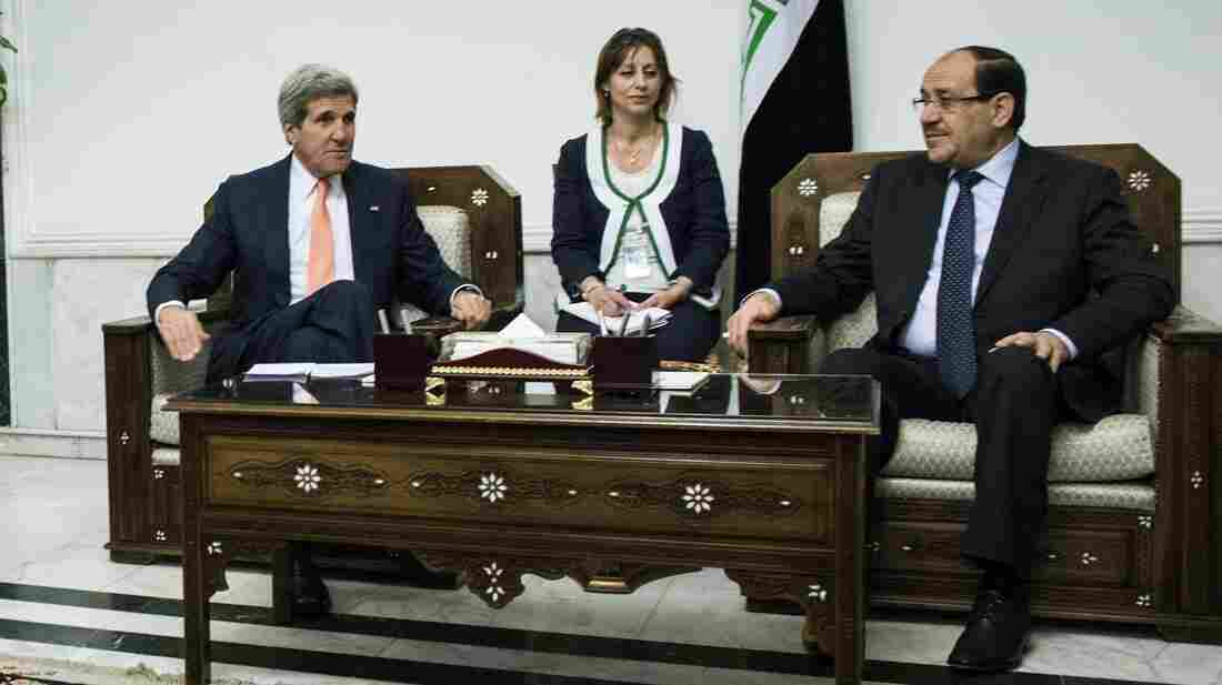 Iraqi Prime Minister Nouri al-Maliki (right) sits with Secretary of State John Kerry on Monday. Kerry was in Baghdad to push for Iraqi unity and stability, as Sunni militants swept through western towns abandoned by security forces.