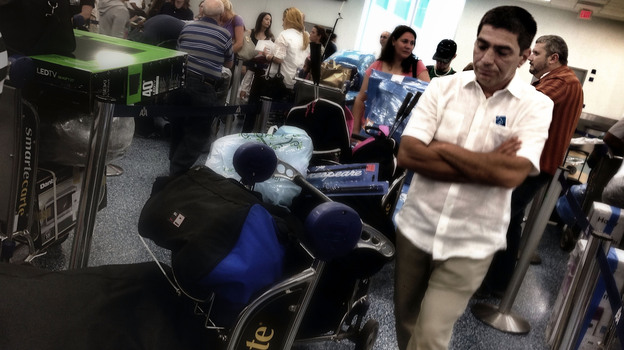 A man stands in line at Miami International airport to board a charter flight to Havana, Cuba. Travelers often fly to Cuba from the U.S. with piles of goods, despite a decades-long trade embargo. (NPR)