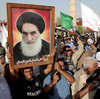 Grand Ayatollah Ali al-Sistani, whose portrait is being held aloft by his Shiite supporters, has emerged in recent weeks to address the crisis facing Iraq.