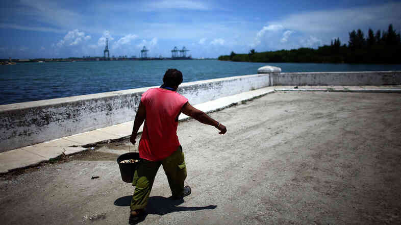 A fisherman walks the streets of Mariel, on Cuba's northwest coast. In the distance, construction is underway on the Port of Mariel, where the government is creating a spec