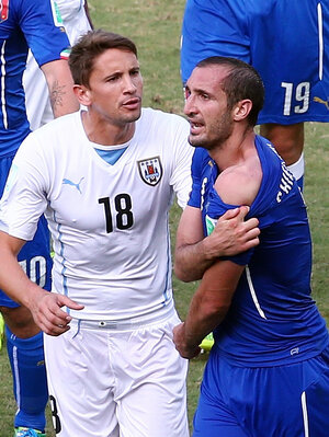 Giorgio Chiellini of Italy pulls down his shirt to show a wound