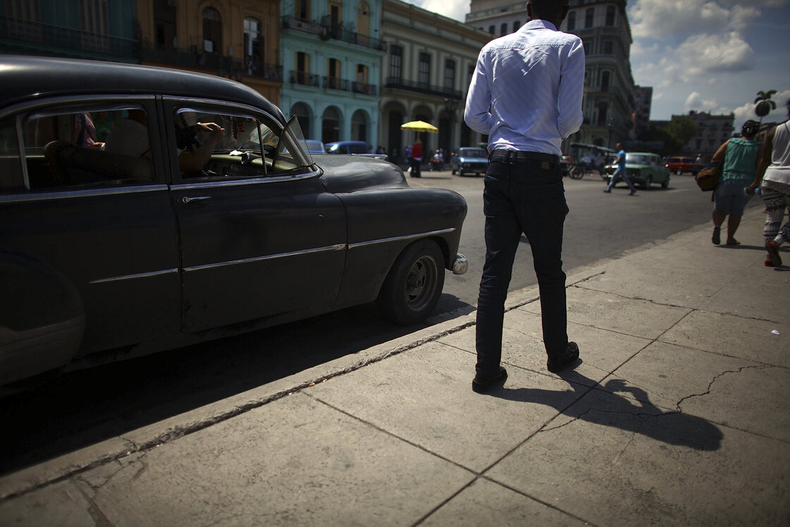 17: Man walking next to black car.
