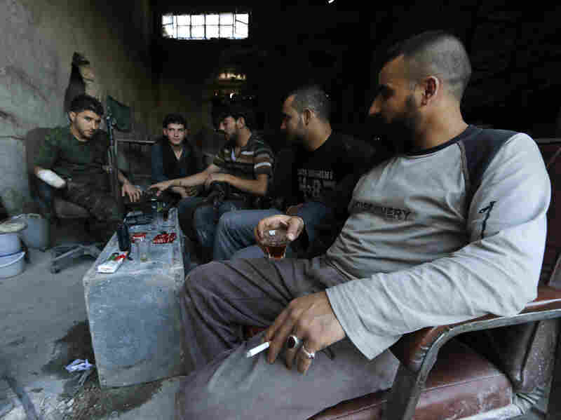 """Rebel fighters drink tea on the front line of Ramouseh, near the Aleppo Artillery School. President Obama has requested $500 million to arm and train """"moderate"""" Syrian rebel groups."""