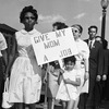 A child carries a sign in demonstration at the Jefferson Bank and Trust Co., against alleged discrimination in hiring practices at the bank in St. Louis on Aug. 31, 1963.