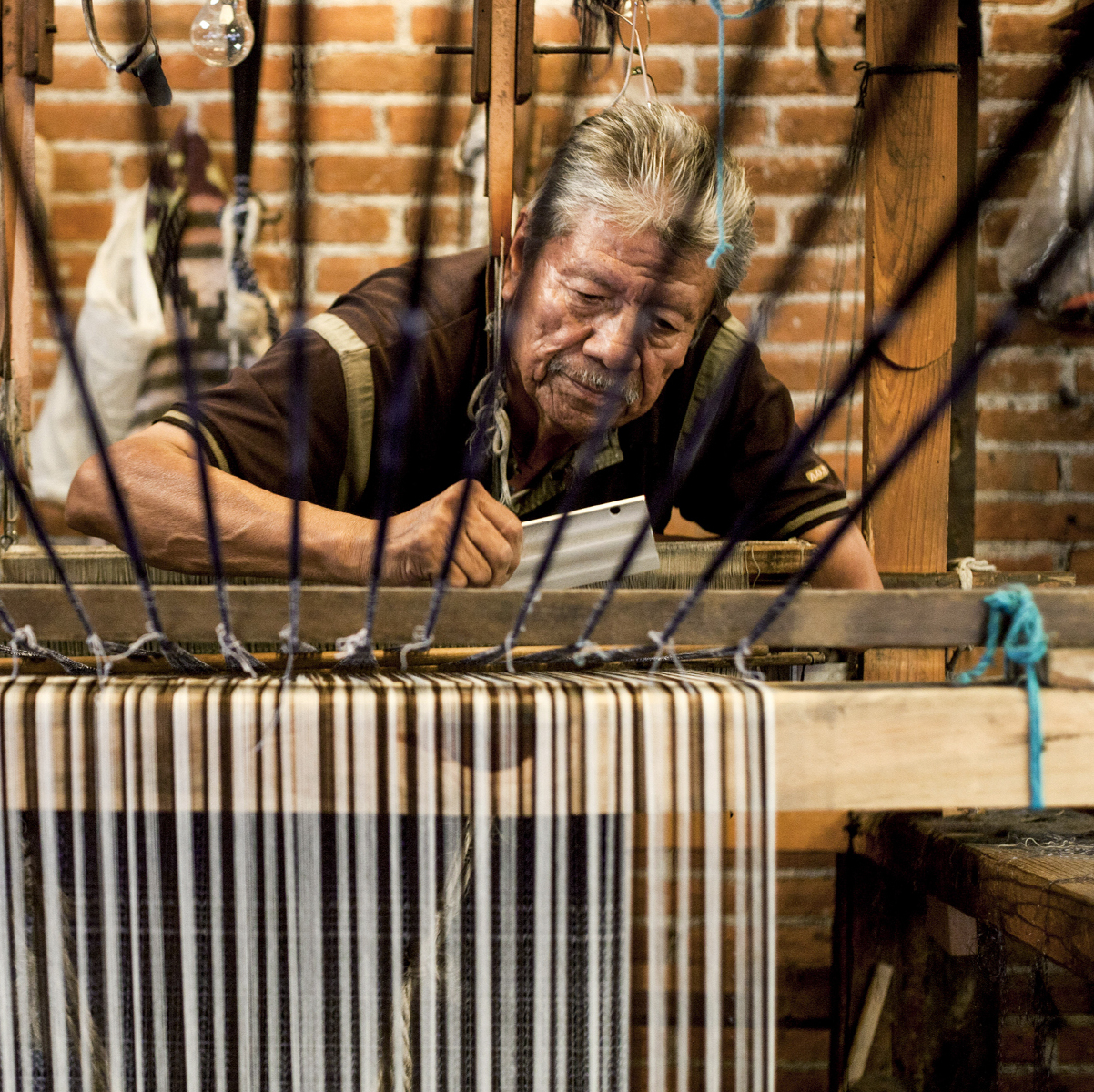 Enrique Antonio Tinoco Jaimes crafts a rebozo on a traditional loom in the rebozo workshop of Don Fermín Escobar in Tenancingo, Mexico. At right, a detail from a rebozo.