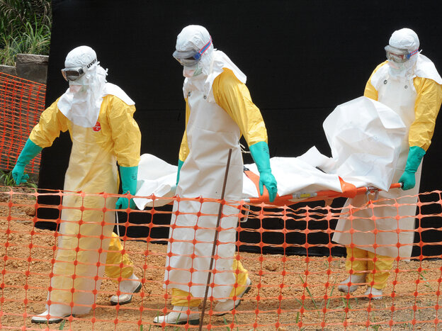 Doctors Without Borders workers transport a body at a center for victims of the Ebola virus in Guekedou, Guinea, in April.