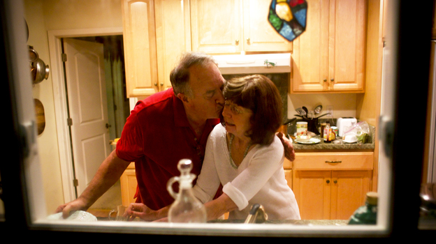 Rick and Marianne wash dishes together. She no longer remembers that he is her husband. (Capital Public Radio)