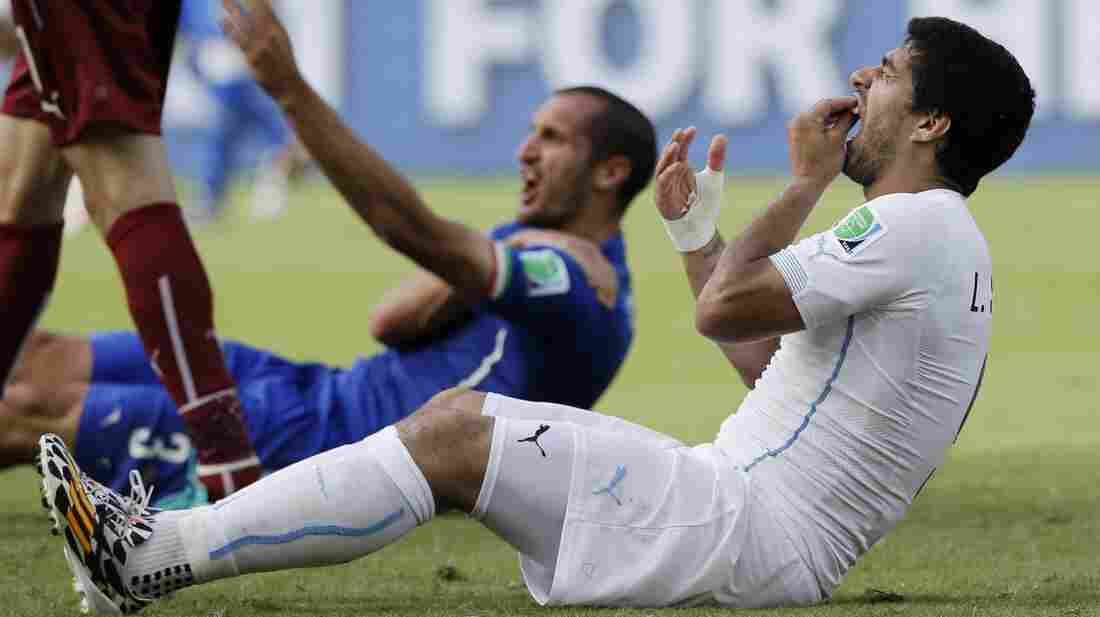 Uruguay's Luis Suarez holds his teeth after biting Italy's Giorgio Chiellini's shoulder during Tuesday's World Cup match between Italy and Uruguay in Brazil. FIFA has banned Suarez for nine games and four months over the incident.