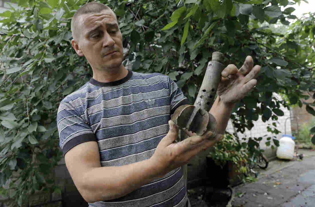 A man who lives in Ukraine's Donetsk region shows part of a shell that exploded in the yard of his house Wednesday, after a reported mortar attack by Ukrainian government forces Tuesday. The area is under a tense cease-fire that will expire Friday.